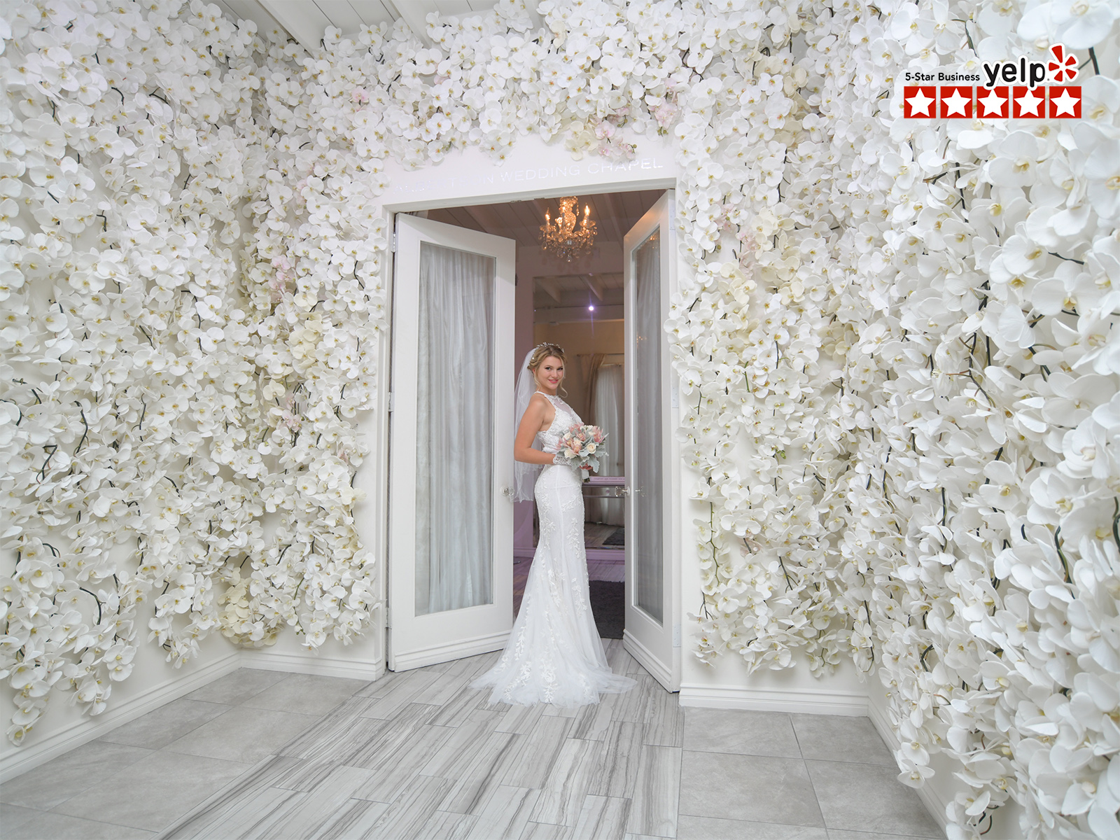 albertson weeding chapel bride standing by flower wall